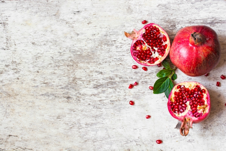 half pomegranate and ripe pomegranate fruit on white rustic background
