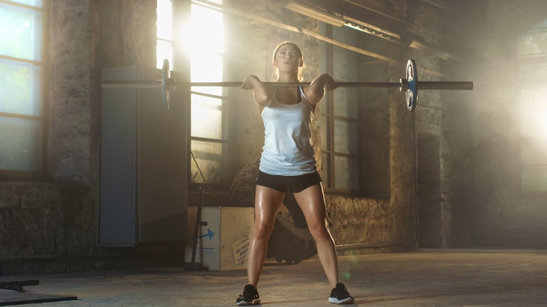 Strong Athletic Woman in Sportswear Lifts Heavy Barbell and Does Squats with it as a Part of Her Cross Fitness Training Routine. Gym is in Remodeled Factory.