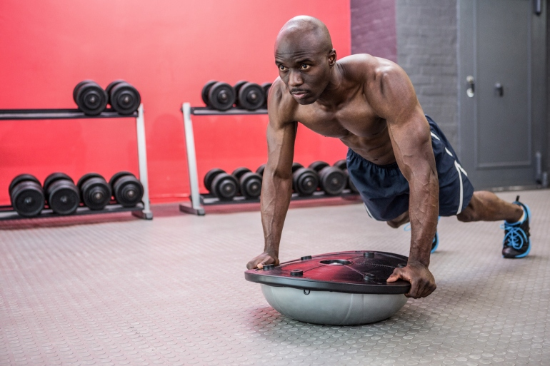 Muscular man exercising with bosu ball