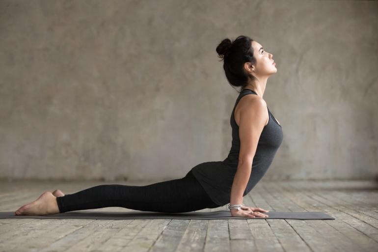 Young woman doing upward facing dog exercise
